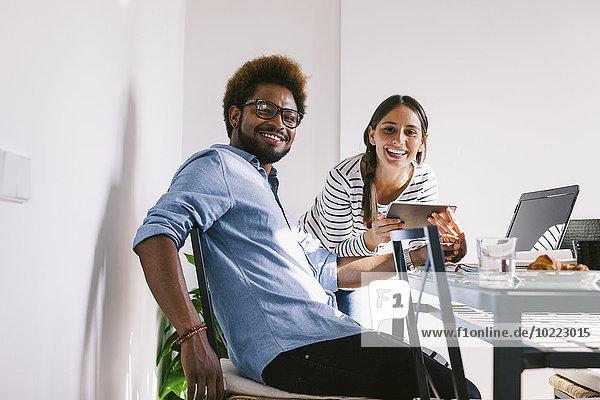 Lächelnder junger Mann und Frau bei der Arbeit mit Laptop und digitalem Tablett im Home Office
