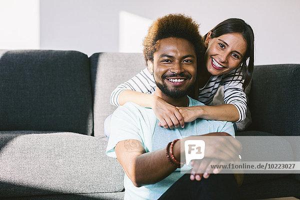 Fröhliches junges Paar auf der Couch sitzend mit den Armen umher