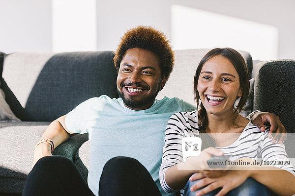 Glückliches junges Paar beim Fernsehen