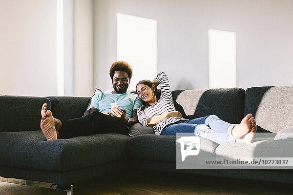 Junges Paar liegt auf der Couch und schaut auf das Smartphone.