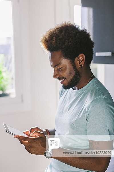 Smiling young man using his phablet at home