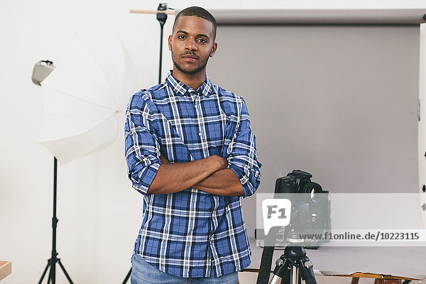 Portrait of young man standing in his photographic studio
