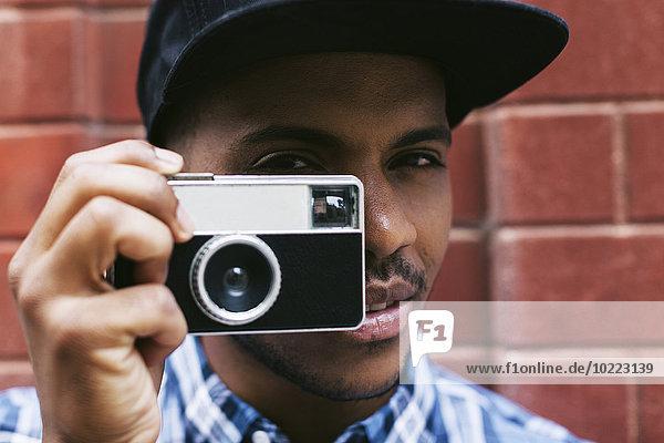 Portrait eines jungen Mannes mit Baseballmütze und Kamera