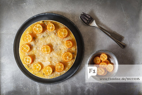 Mango-Passionsfruchtkuchen mit Kumquatscheiben verziert