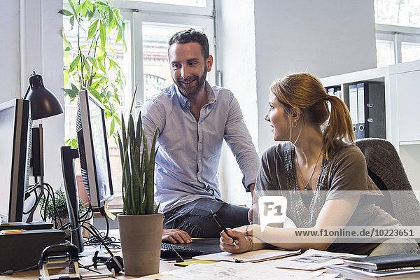 Mann und Frau im Büro im Gespräch am Schreibtisch