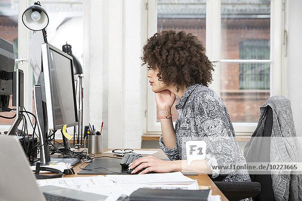 Junge Frau im Büro bei der Arbeit am Computer