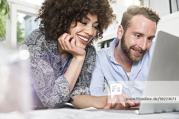 Lächelnder Mann und Frau im Büro teilen sich Laptop
