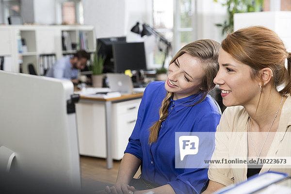 Zwei lächelnde Frauen im Büro mit Blick auf den Computerbildschirm