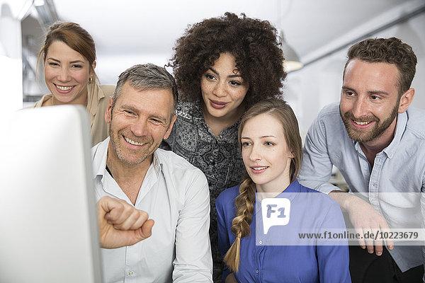 Lächelnde Kollegen im Büro mit Blick auf den Monitor