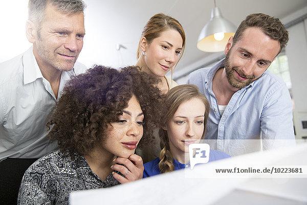 Kollegen im Büro beim Blick auf den Plan