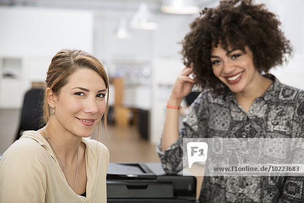Portrait of two smiling colleagues in office