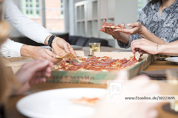 Kollegen im Büro teilen sich Pizza