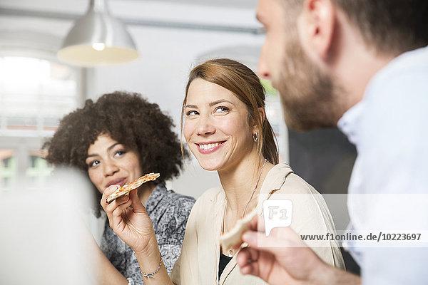 Drei Kollegen im Büro beim Pizzaessen