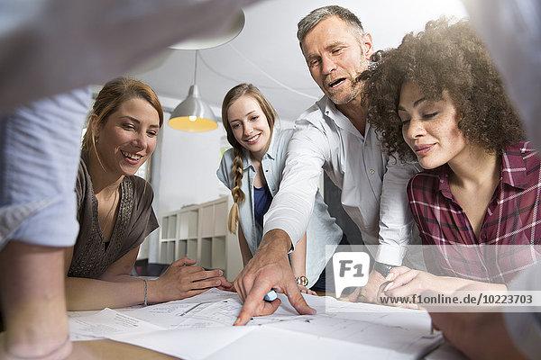 Kollegen im Büro diskutieren über den Bauplan