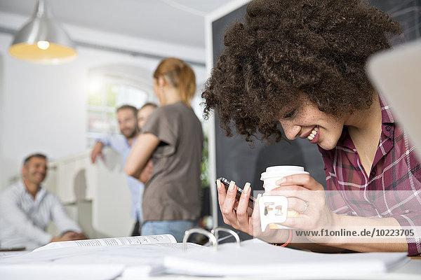 Lächelnde Frau mit Handy und Kaffee für das Büro