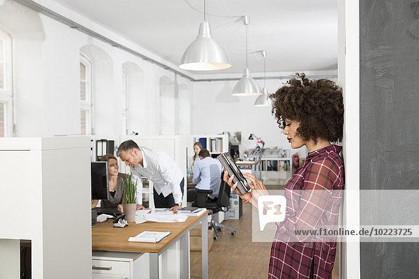 Frau im Büro mit digitalem Tablett und Kollegen im Hintergrund