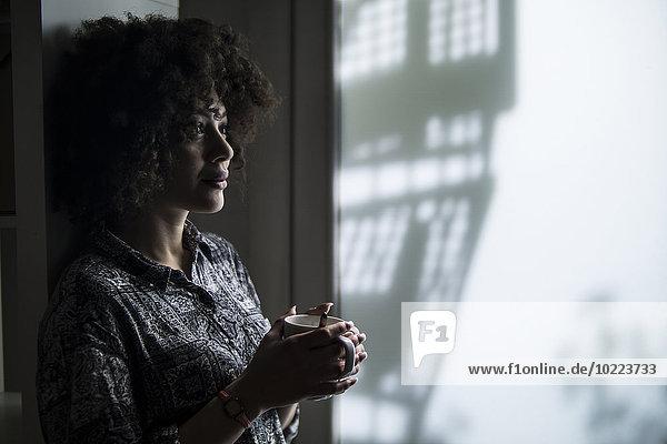 Eine dunkelhaarige junge Frau denkt.