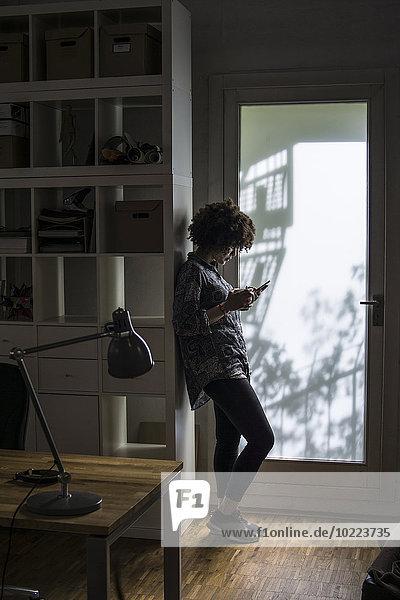 Junge Frau mit Handy am Schrank gelehnt