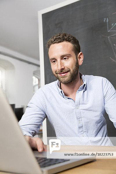 Junger Mann im Büro mit Laptop