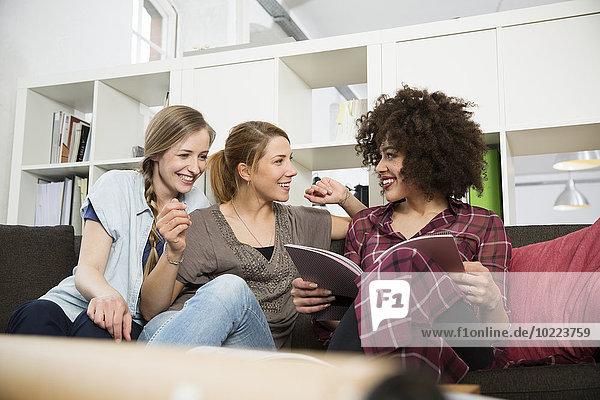 Drei junge Frauen im Büro sitzend auf der Couch mit Magazin