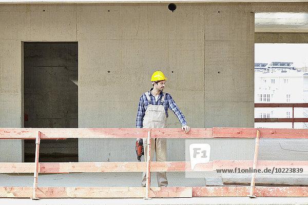 Mann mit Schutzhelm auf der Baustelle am Geländer stehend