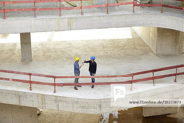 Zwei Männer mit Schutzhelmen  die auf der Baustelle klirren.