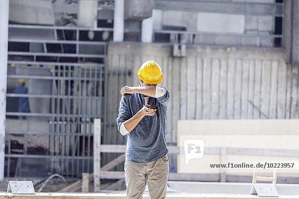 Mann mit Handy mit Schutzhelm auf der Baustelle