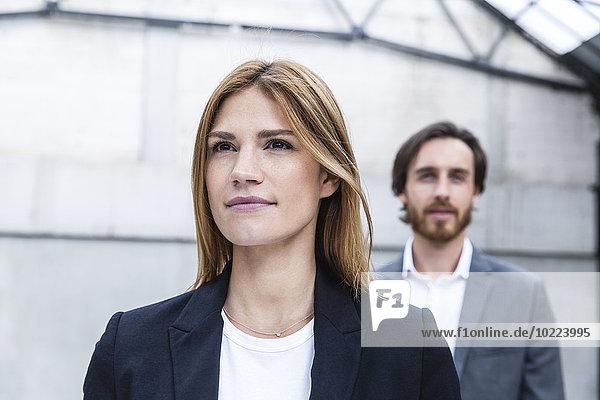 Portrait der Geschäftsfrau mit ihrem Partner im Hintergrund
