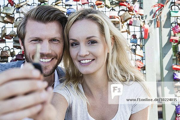 Deutschland  Köln  Porträt eines lächelnden jungen Paares mit Schlüssel zum Liebesschloss