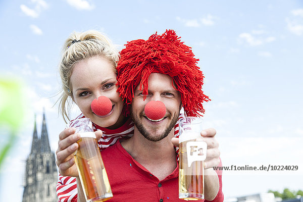 Germany  Cologne  young couple celebrating carnival dressed up as clowns