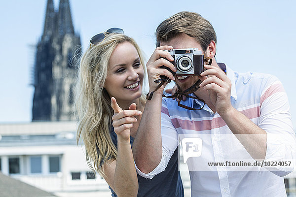 Germany  Cologne  young couple taking a picture with camera