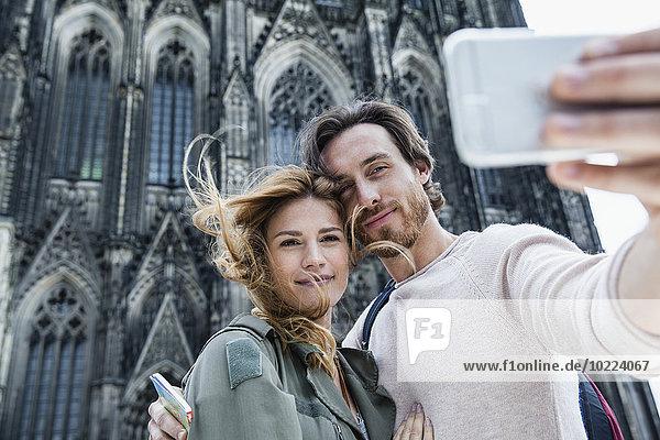 Deutschland  Köln  Porträt eines jungen Ehepaares vor dem Kölner Dom