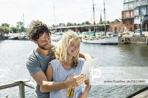 Deutschland  Lübeck  glückliches Paar am Hafen mit digitalem Tablett