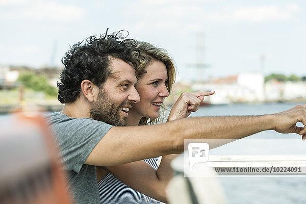 Deutschland  Lübeck  lächelndes Paar  das auf etwas zeigt