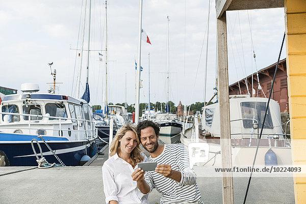 Deutschland  Lübeck  lächelndes Paar im Yachthafen mit Smartphone
