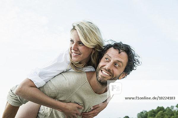 Lächelnder Mann mit Huckepack-Frau