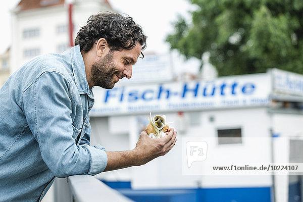 Lächelnder Mann mit Fischsandwich