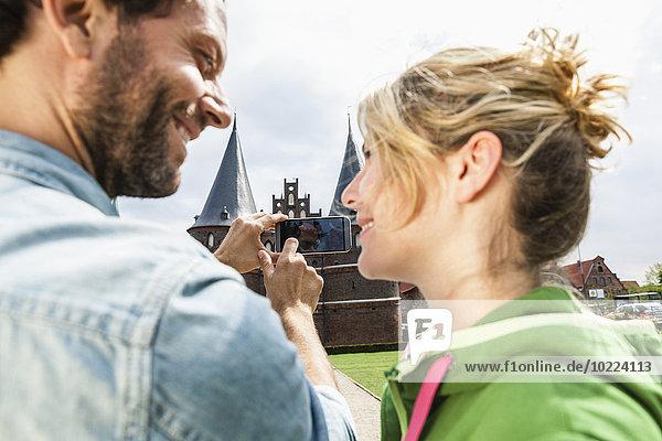 Deutschland  Lübeck  Paar beim Fotografieren vor dem Holstentor