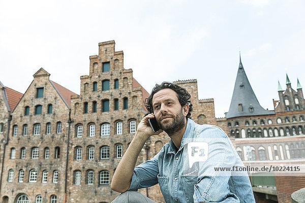 Deutschland  Lübeck  Mann am Handy in der Stadt