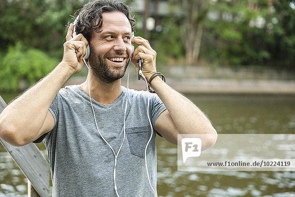 Glücklicher Mann beim Musikhören am Wasser