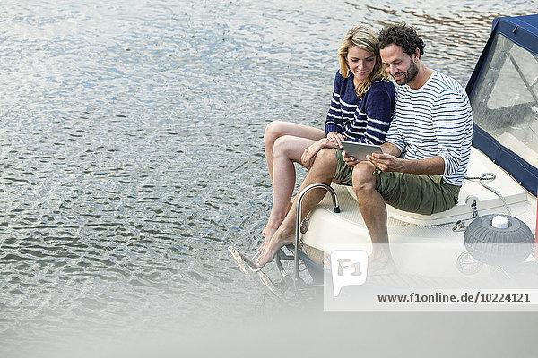 Paar auf dem Boot mit digitalem Tablett