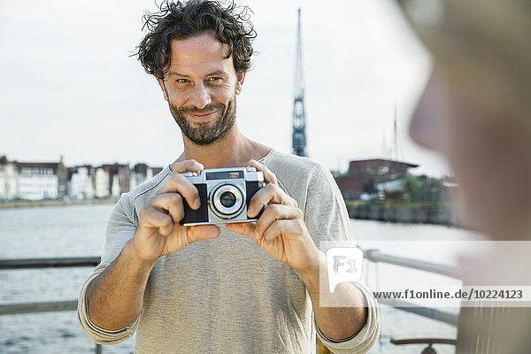 Deutschland  Lübeck  Mann beim Fotografieren am Wasser