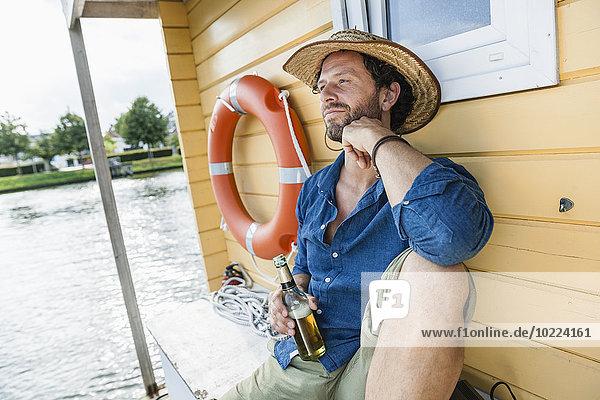 Entspannter Mann auf einem Hausboot mit Bierflasche