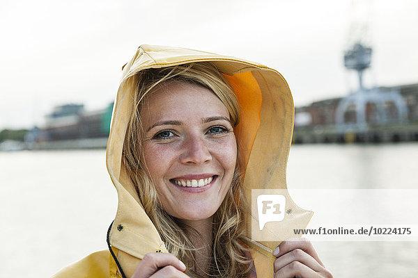 Porträt einer jungen Frau im Regenmantel am Wasser