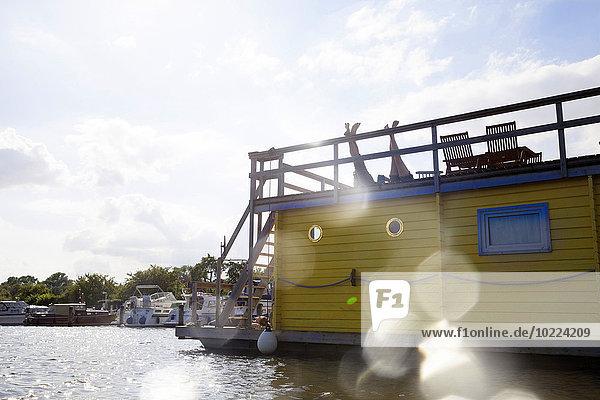 Beine eines Paares auf der Dachterrasse eines Hausbootes