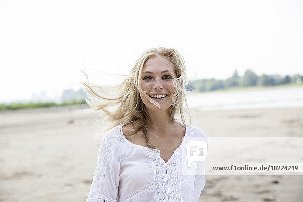 Porträt einer lächelnden blonden Frau mit blasendem Hait am Strand