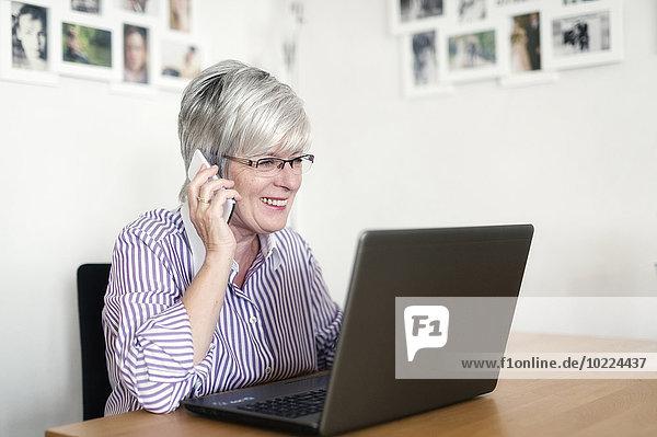 Portrait einer älteren Frau mit Laptop-Telefonie mit Smartphone
