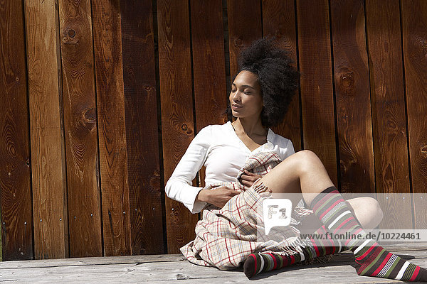 Sunbathing young woman leaning on wooden wall