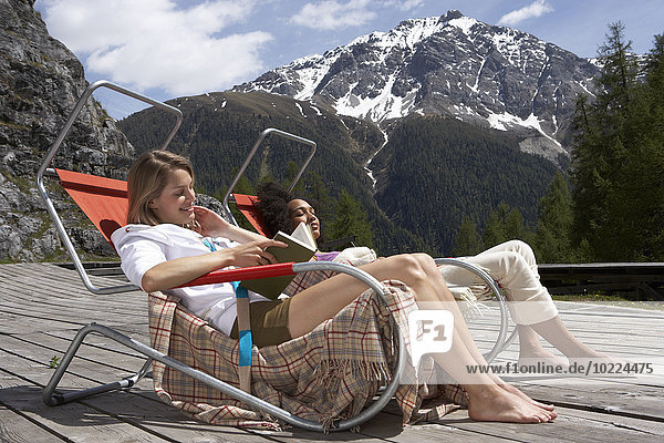 Switzerland  two young women sitting on deck chairs on sun deck