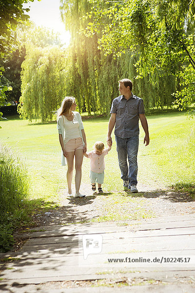 Eltern  die mit ihrem kleinen Sohn im Park spazieren gehen.